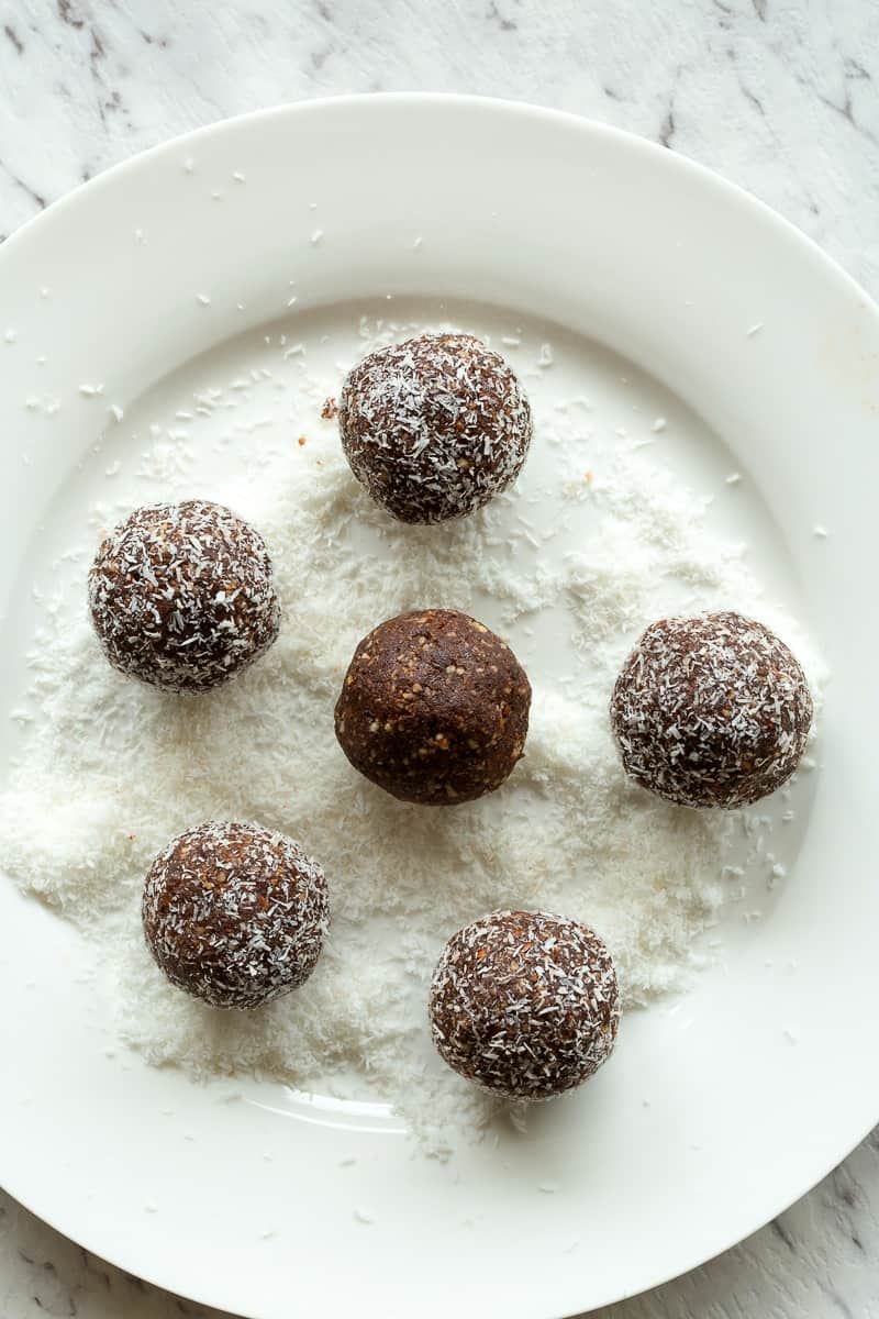 chocolate coconut bliss balls on shredded coconut