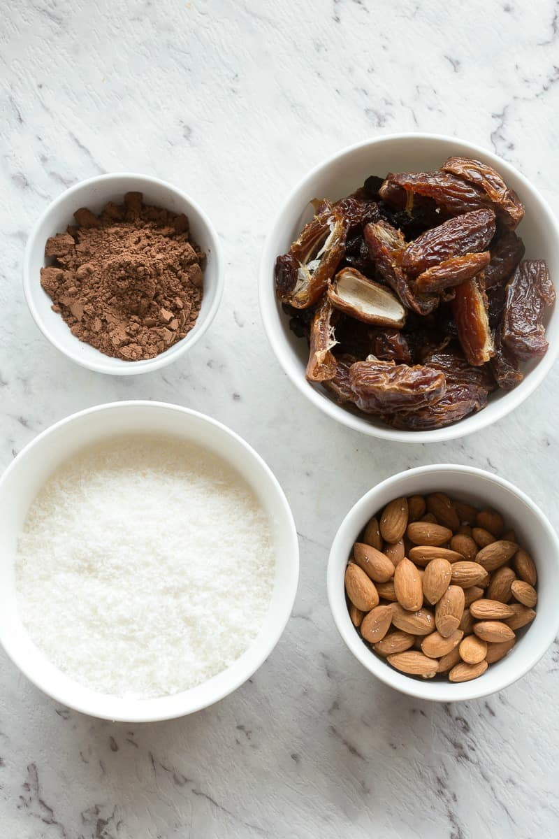 cocoa powder, pitted dates, shredded coconut and almonds in bowls
